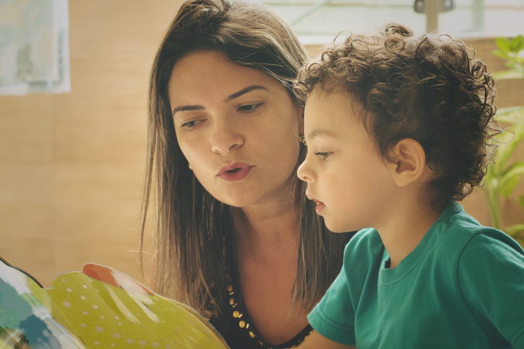 A mom reads a book with her young son