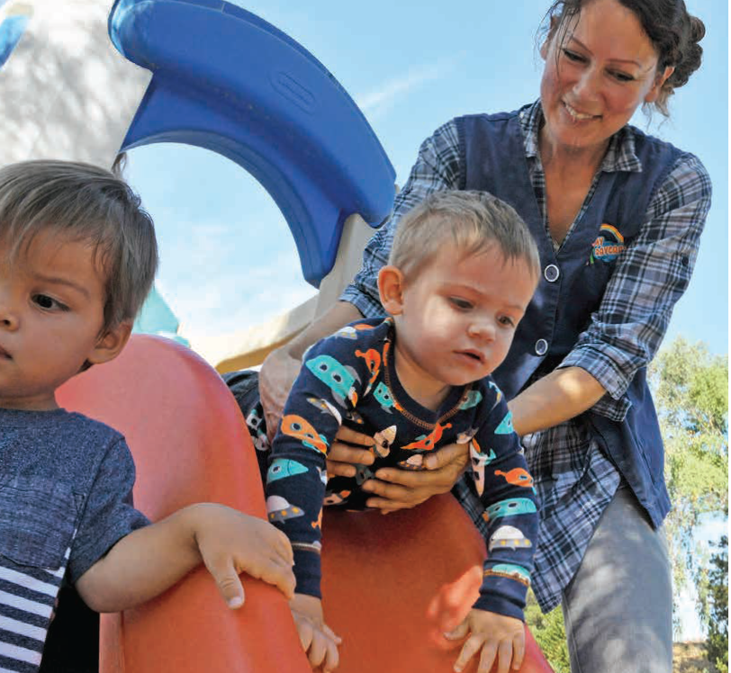 Child care provider Rebekah plays with children on a slide.