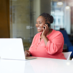 A woman sitting at a computer desk smiles as she talks on the phone