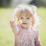 A young girl hands a flower toward the camera