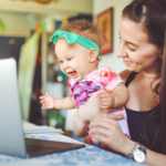 A woman holds a baby up to her laptop