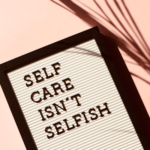 """A tablet showing the words, """"self care isn't selfish"""""""