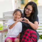 A mom and daughter use their hands to make a heart