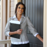 A professionally dressed woman holding a notebook opens a door