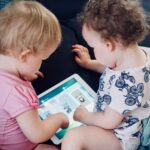 Two toddlers look at a tablet