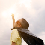 A child dressed as a superhero holds his fist up to the sky