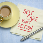 """A cup of tea on a yellow saucer sits next to a napkin that says, """"Self care isn't selfish"""""""