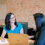 Two women talk in an office setting