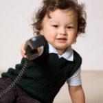 A toddler holds a landline phone